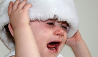 Crying baby in a Santa hat