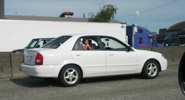no words for this, really - kid allowed to hang out window of moving car on freeway