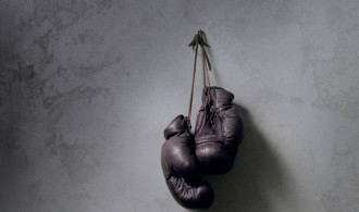 Photo of a pair of boxing gloves hanging on the wall.