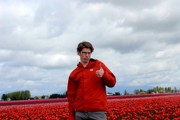 Zac the SEO lead in a tulip field giving a thumbs up