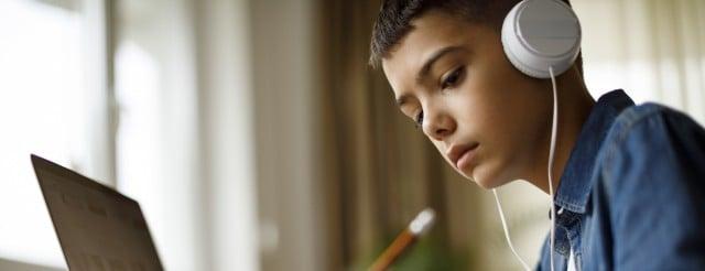 Teenage boy listening to music while doing homework