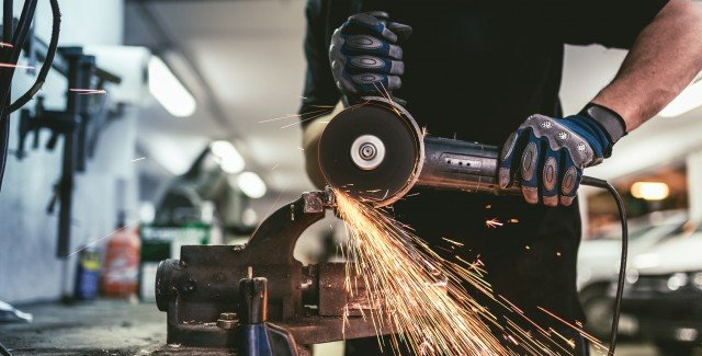 Industry worker with steel angle grinder