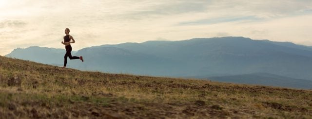 Female runner in open field with mountains in the background